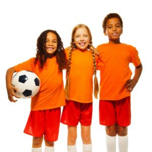 Kids in sports uniforms holding a soccer ball