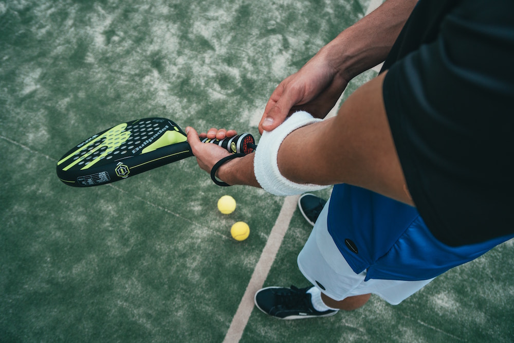 common sports injuries, man holding tennis racket