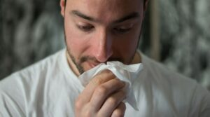 man with tissue to nose suffering from seasonal allergies