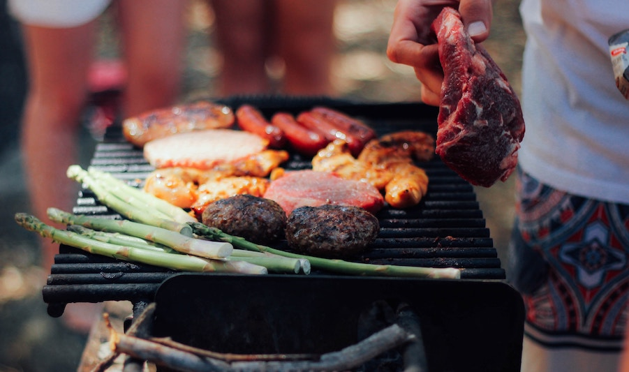 person grilling meat and veggies - food safety to prevent foodborne illness