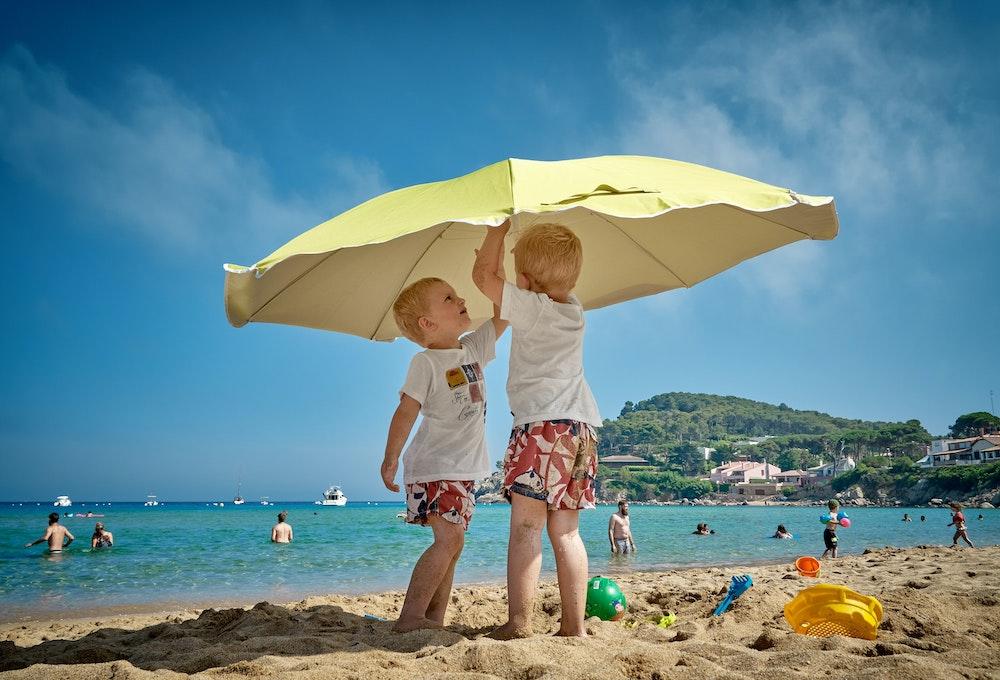 kids under beach umbrella to prevent sunburn