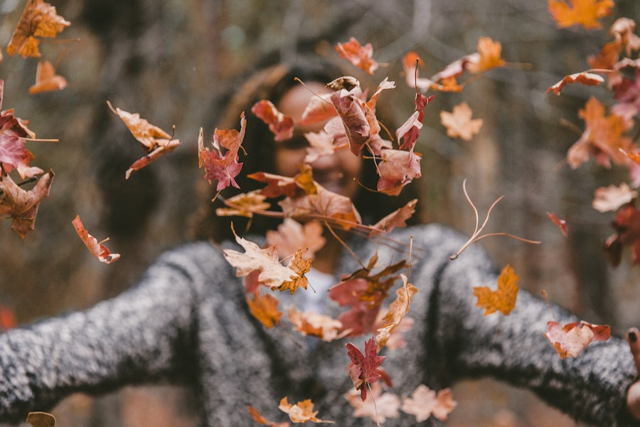 woman playing with fallen leaves - fall health concerns