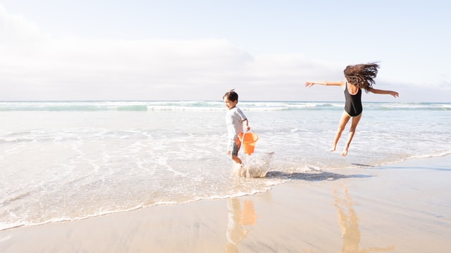 kids playing at the beach wearing sunscreen for protection